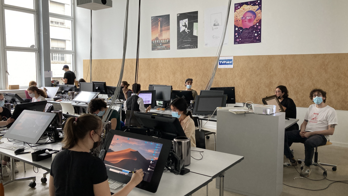 A well lit atelier space with high ceilings is the perfect place for the Living Lines Workshop. Tables are filled with Cintique drawing tablets, students are drawing and Veronica L. Montaño and Frederic Siegel are teaching.